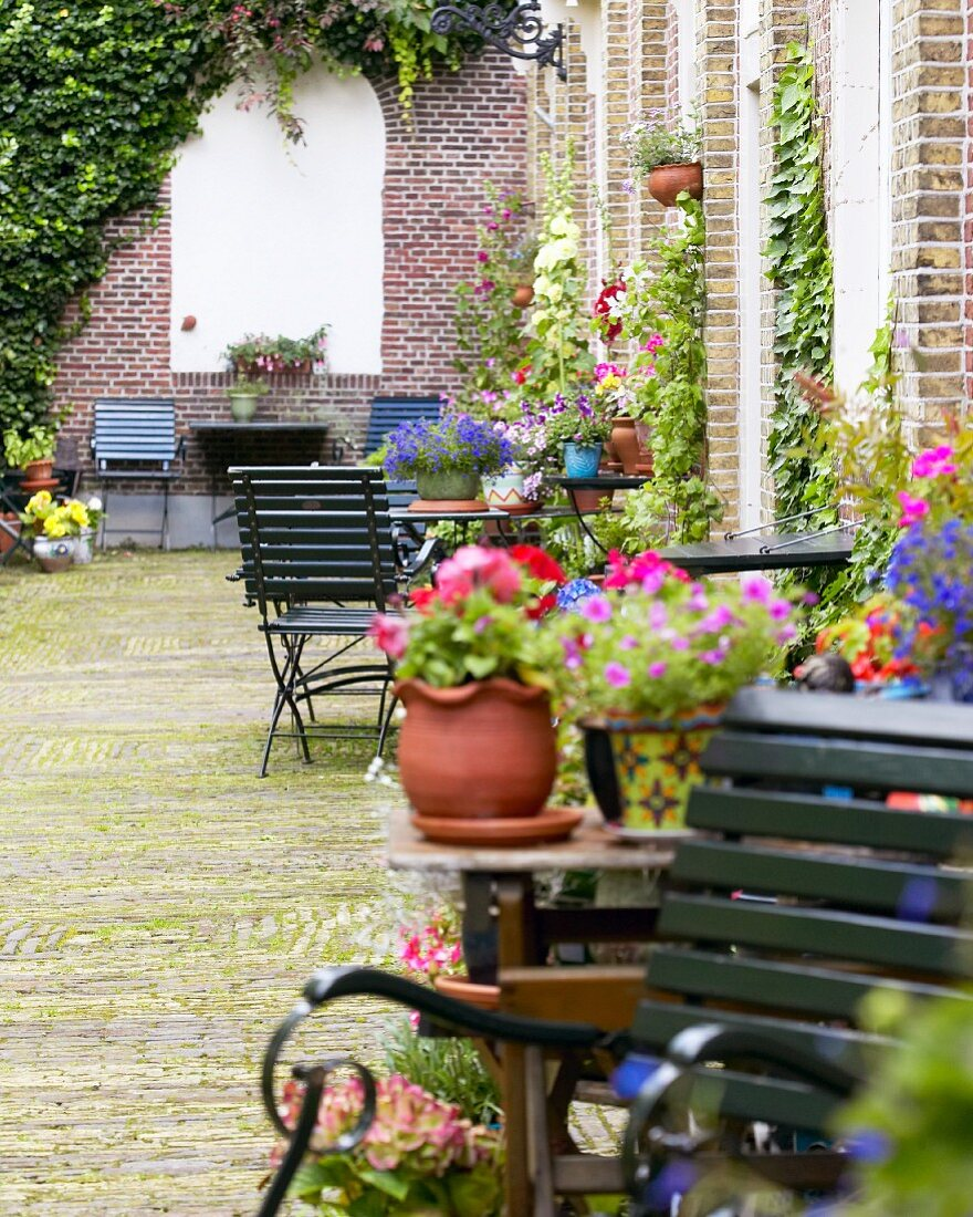 An idyllic inner courtyard with flowers and garden furniture against a brick facade