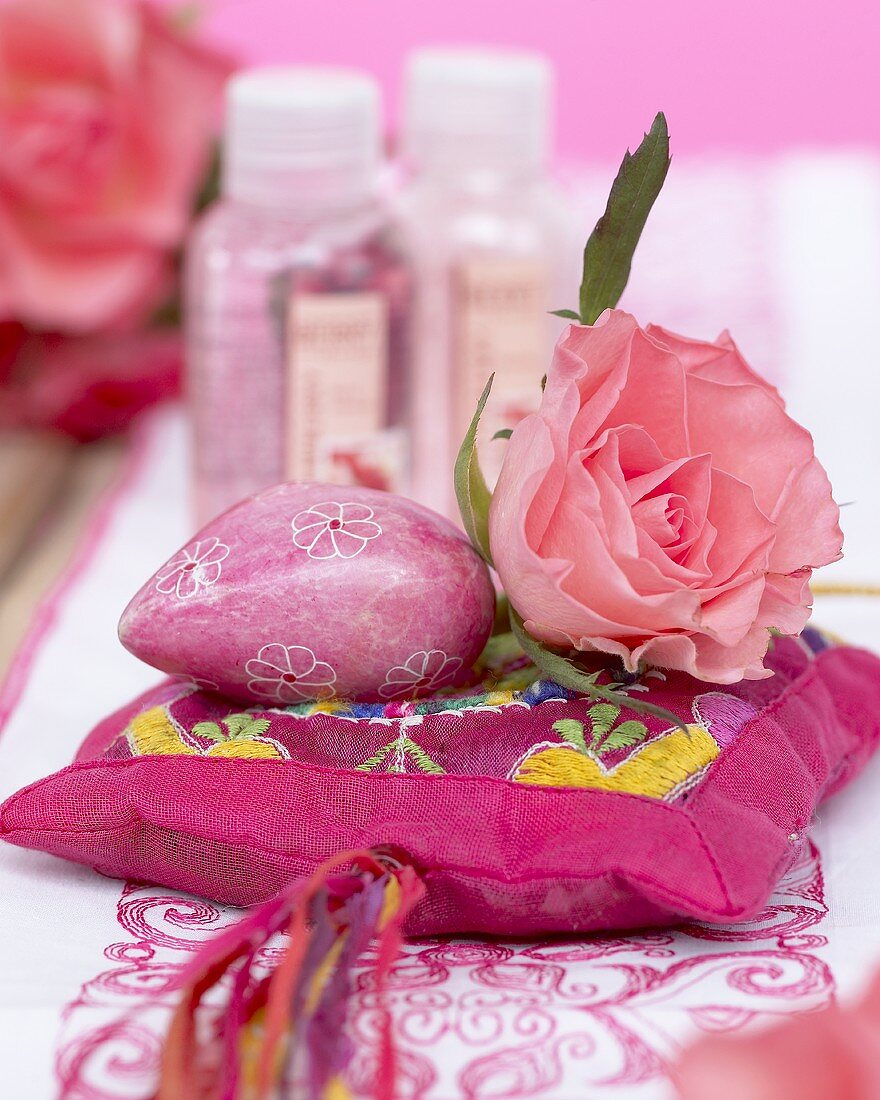 Pink rose on silk cushion, bath products