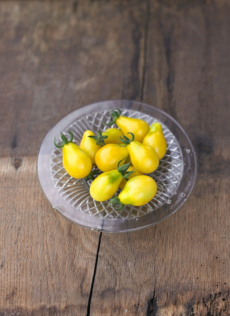 Yellow pear tomatoes on glass plate