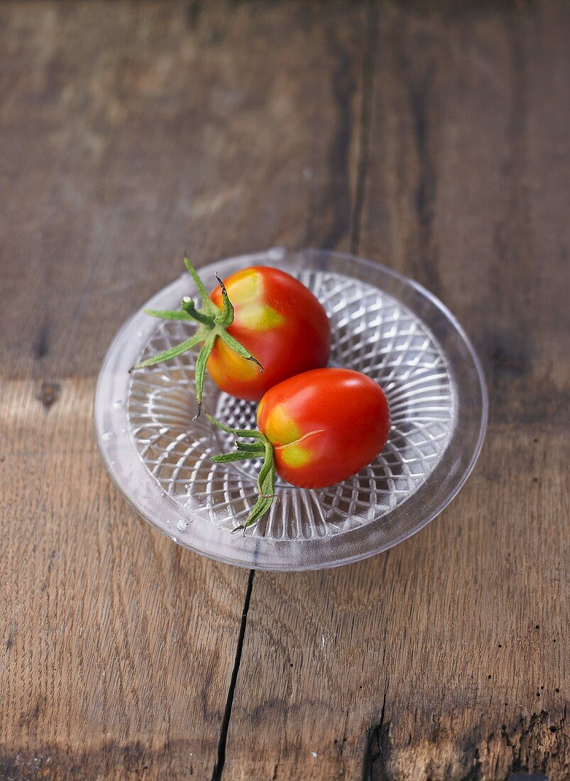 Two tomatoes, variety 'Omas Beate', on glass plate