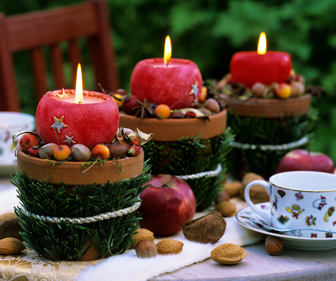 Three candles in terracotta pots decorated for Christmas