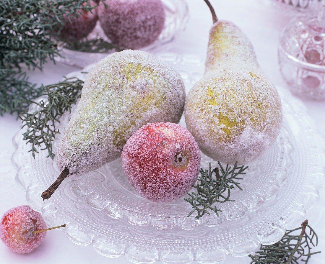 Gezuckerte Birnen und Äpfel auf Kristallglasplatte