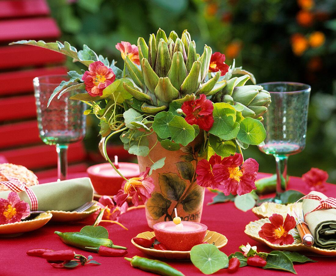 Arrangement of artichokes, nasturtiums and chillies