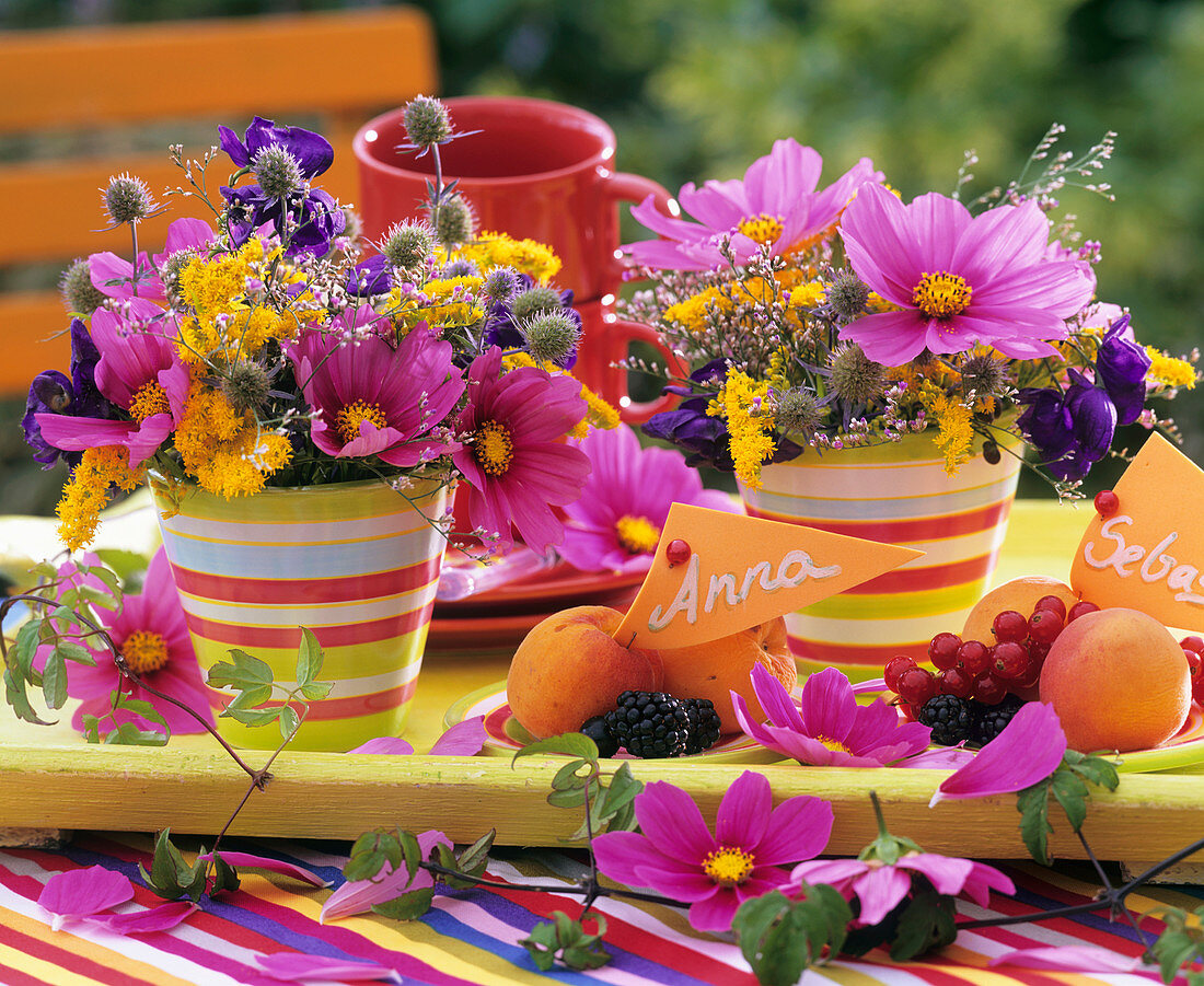 Colourful flower arrangements & plates of fruit with place-cards
