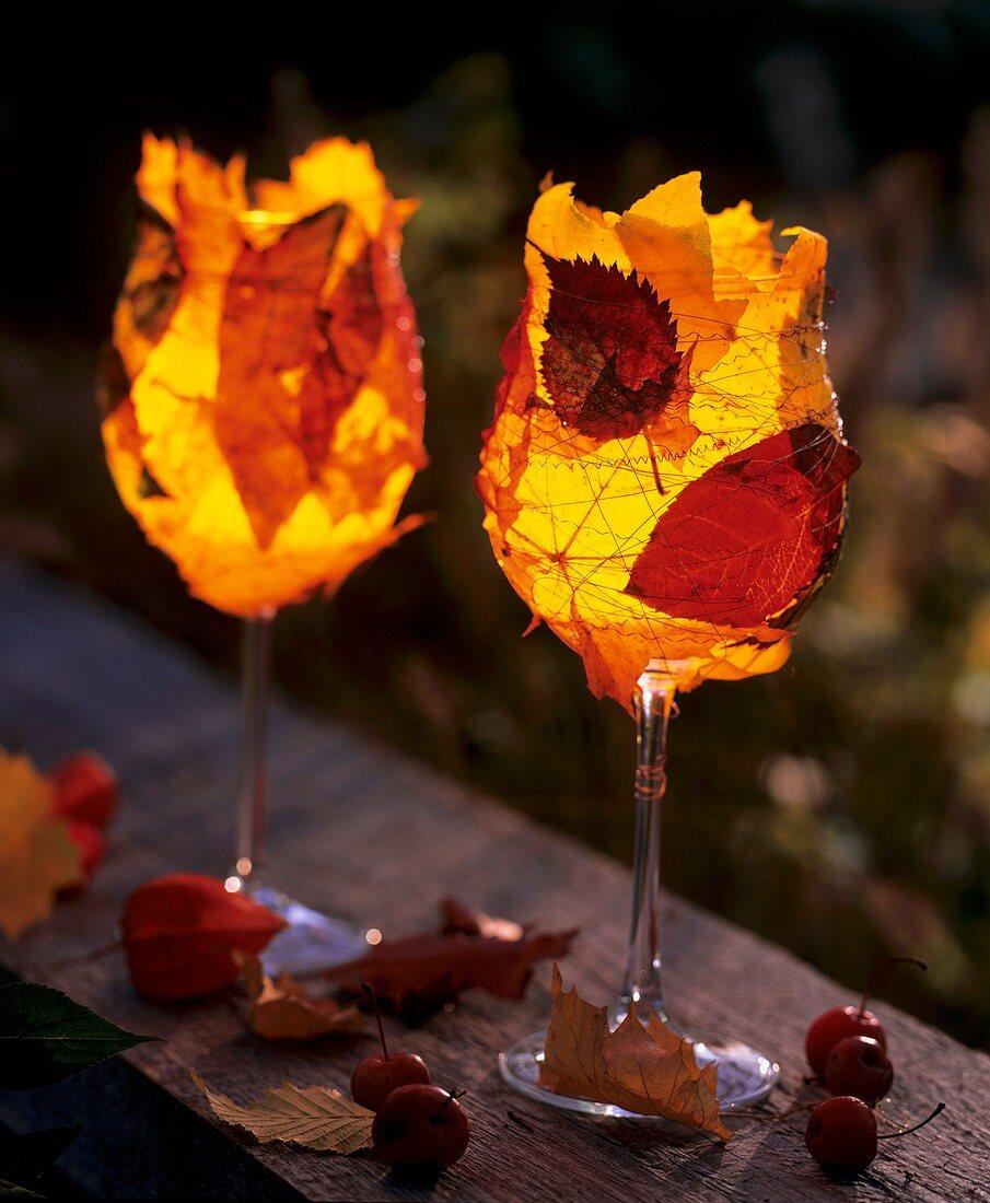 Weingläser mit Teelichtern, umwickelt mit buntem Herbstlaub