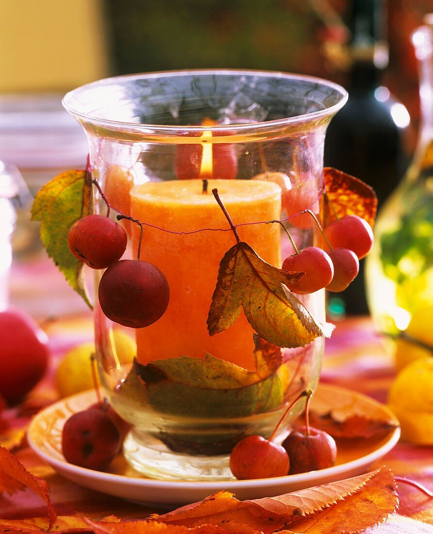 Glass windlight with orange candle, with ornamental apples