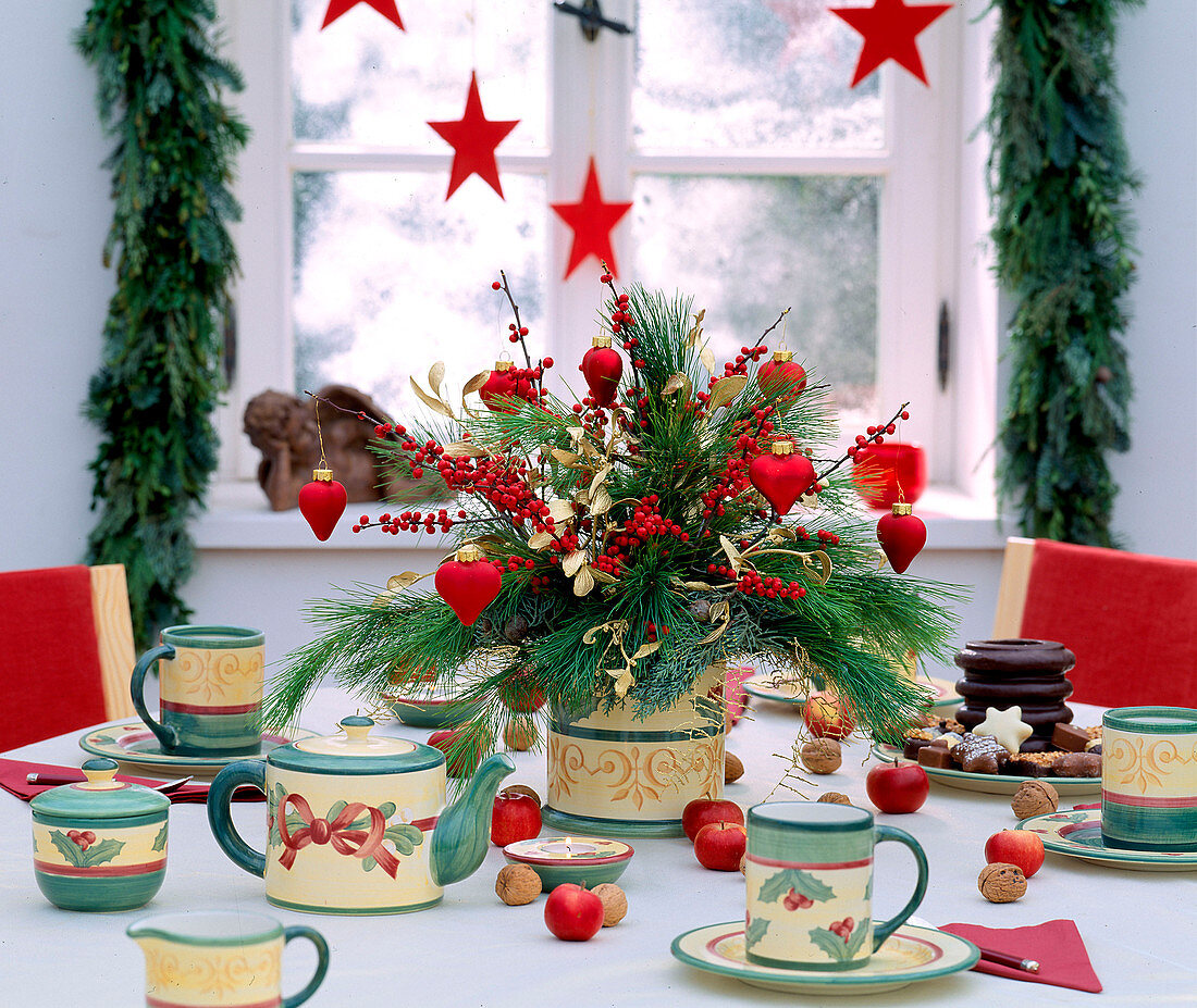 Festive table laid for coffee with arrangement of pine