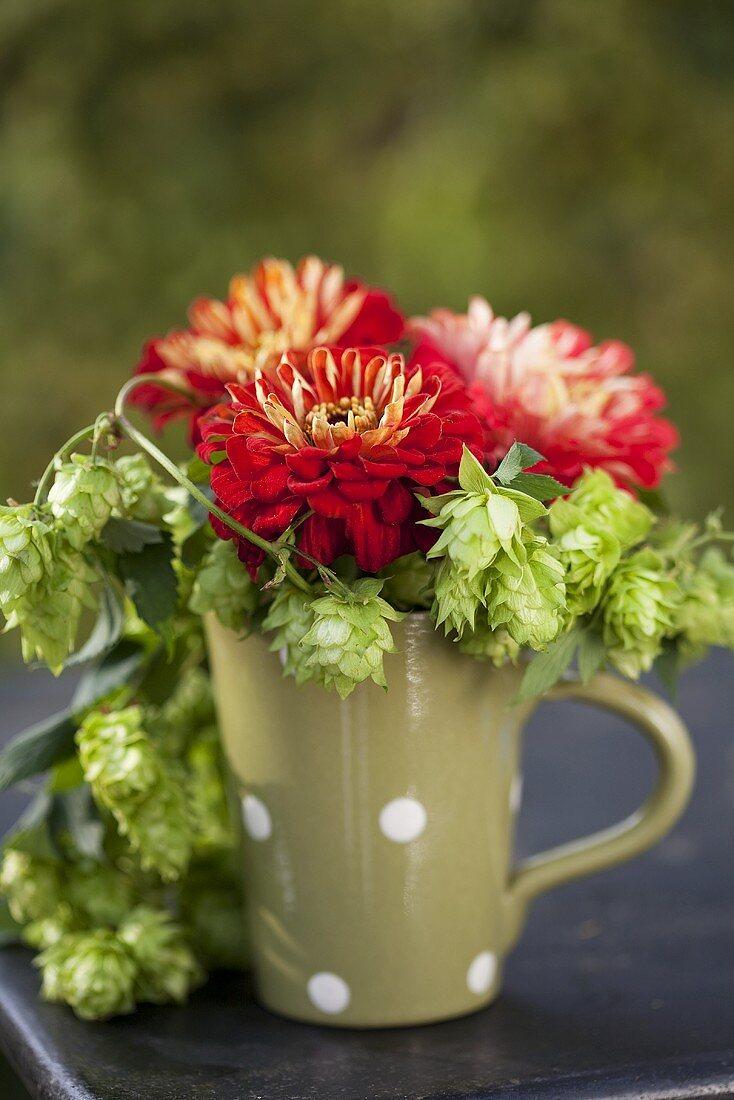 Pompom dahlias and hops in ceramic mug