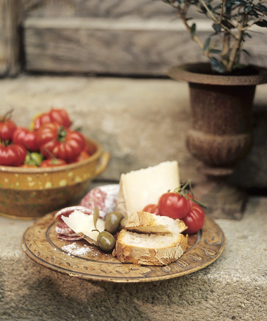 Italian snack: cheese, hard cured sausage, olives & tomatoes