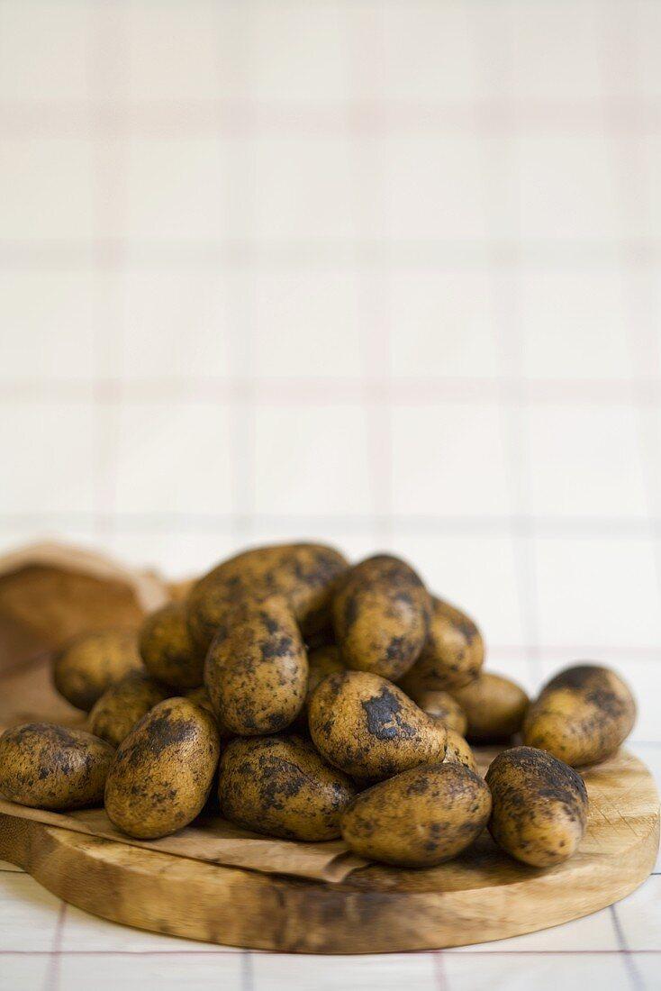 Fresh potatoes on a wooden board