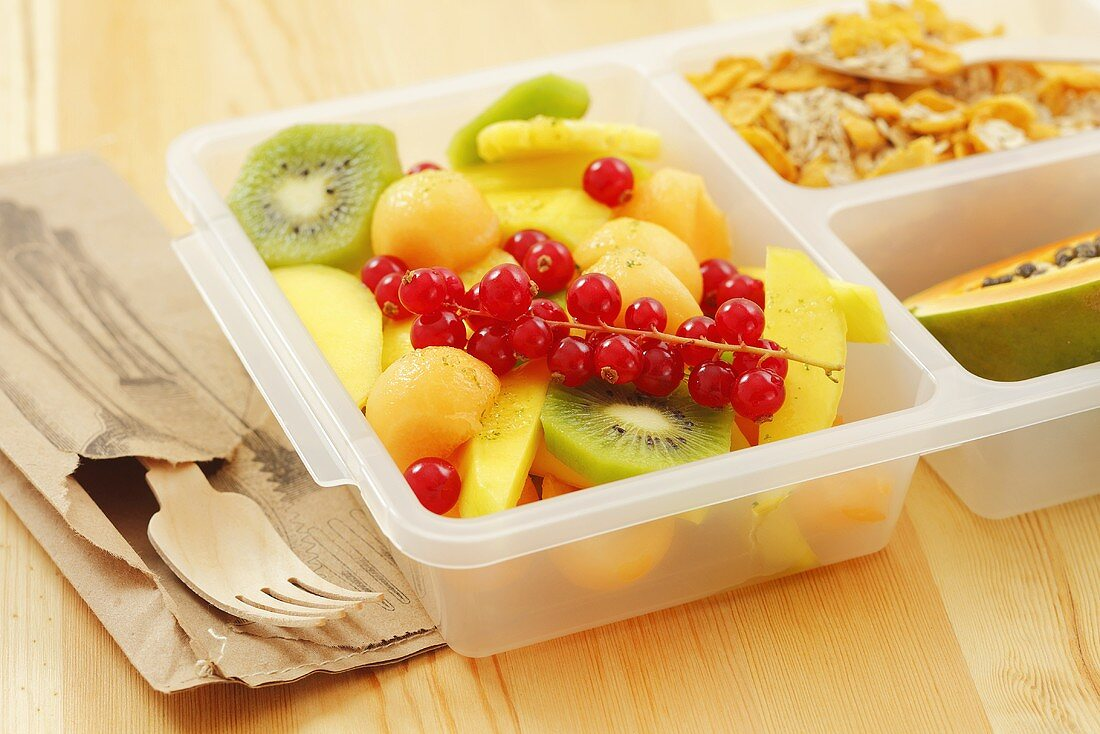 Fruit salad, muesli and half a papaya in a plastic box