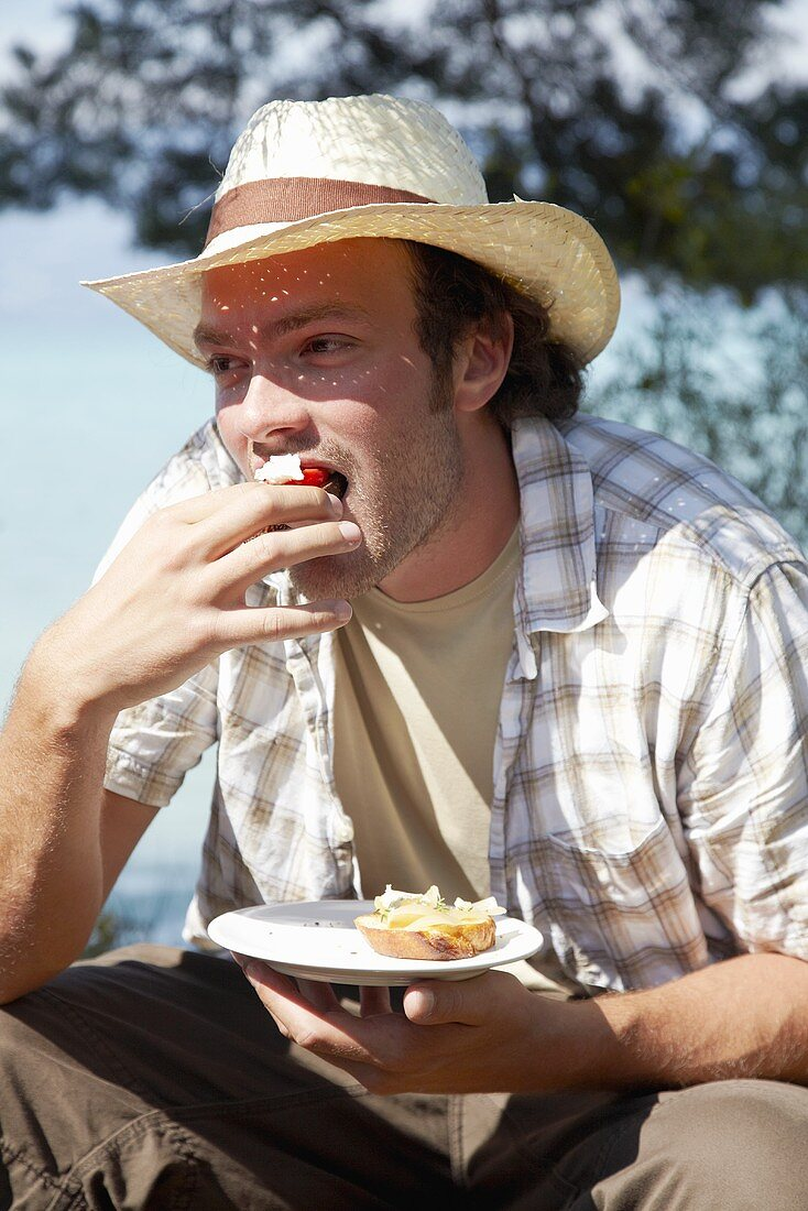 Young man in straw hat eating crostini