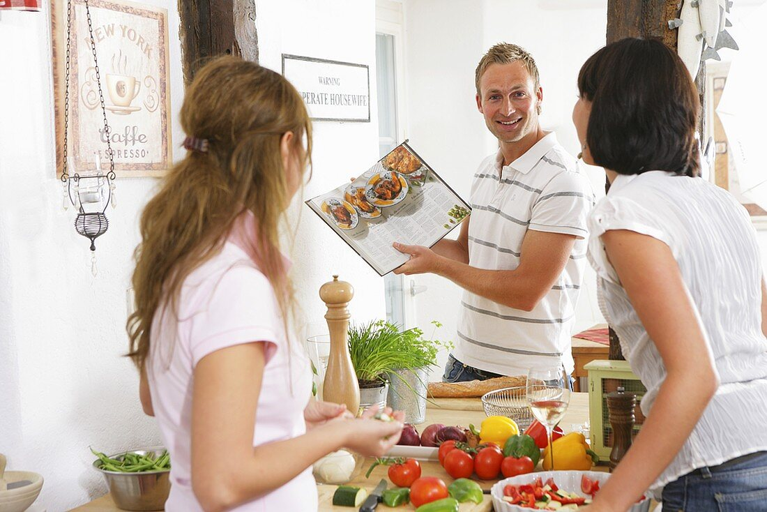 Three young people with vegetables & cookery book in kitchen