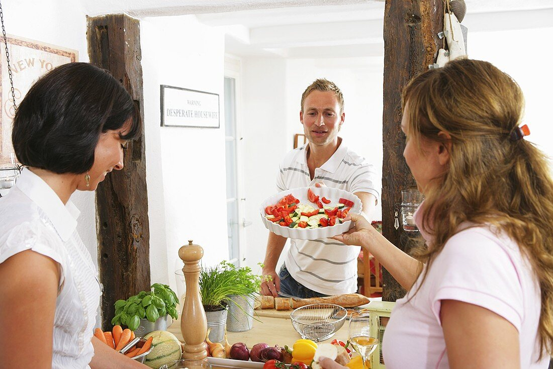 Young woman passing quiche dish with vegetables to young man