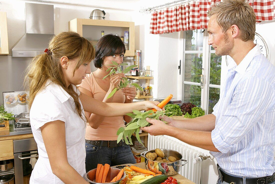Three young people with vegetables and herbs in kitchen