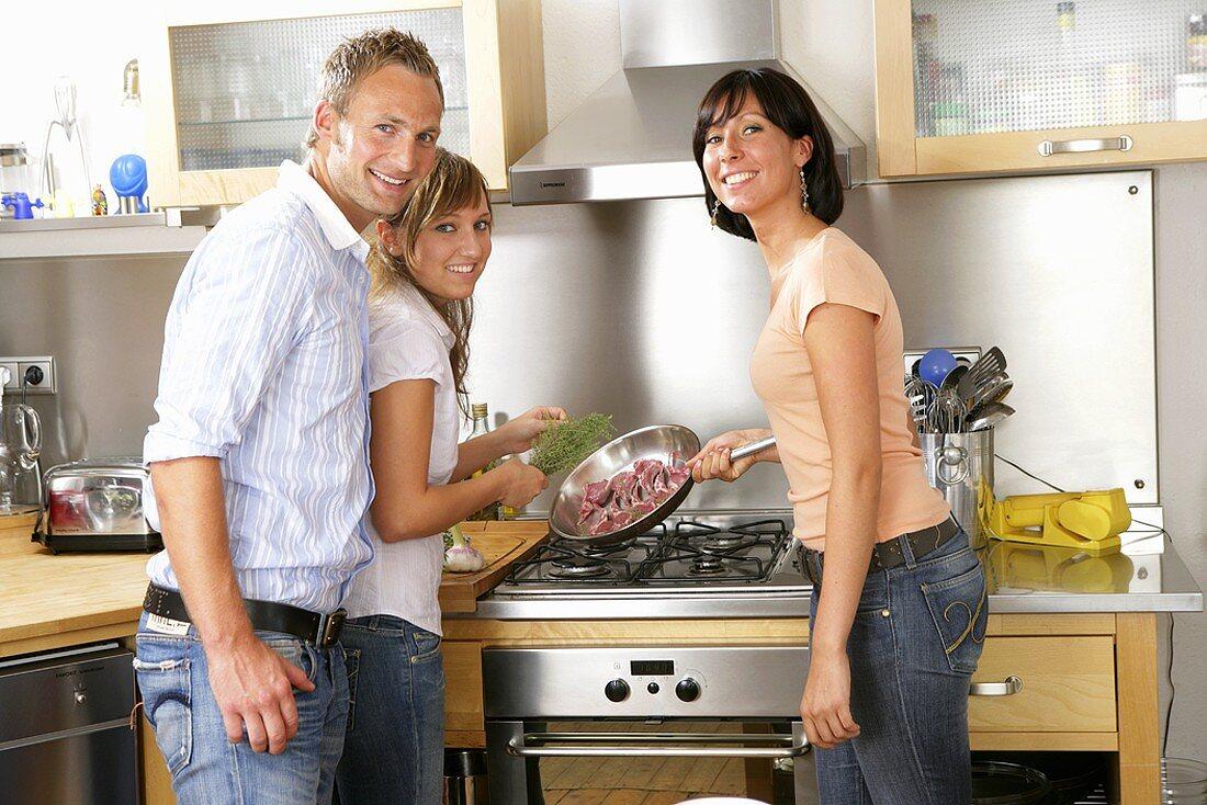 Three young people preparing a lamb dish together