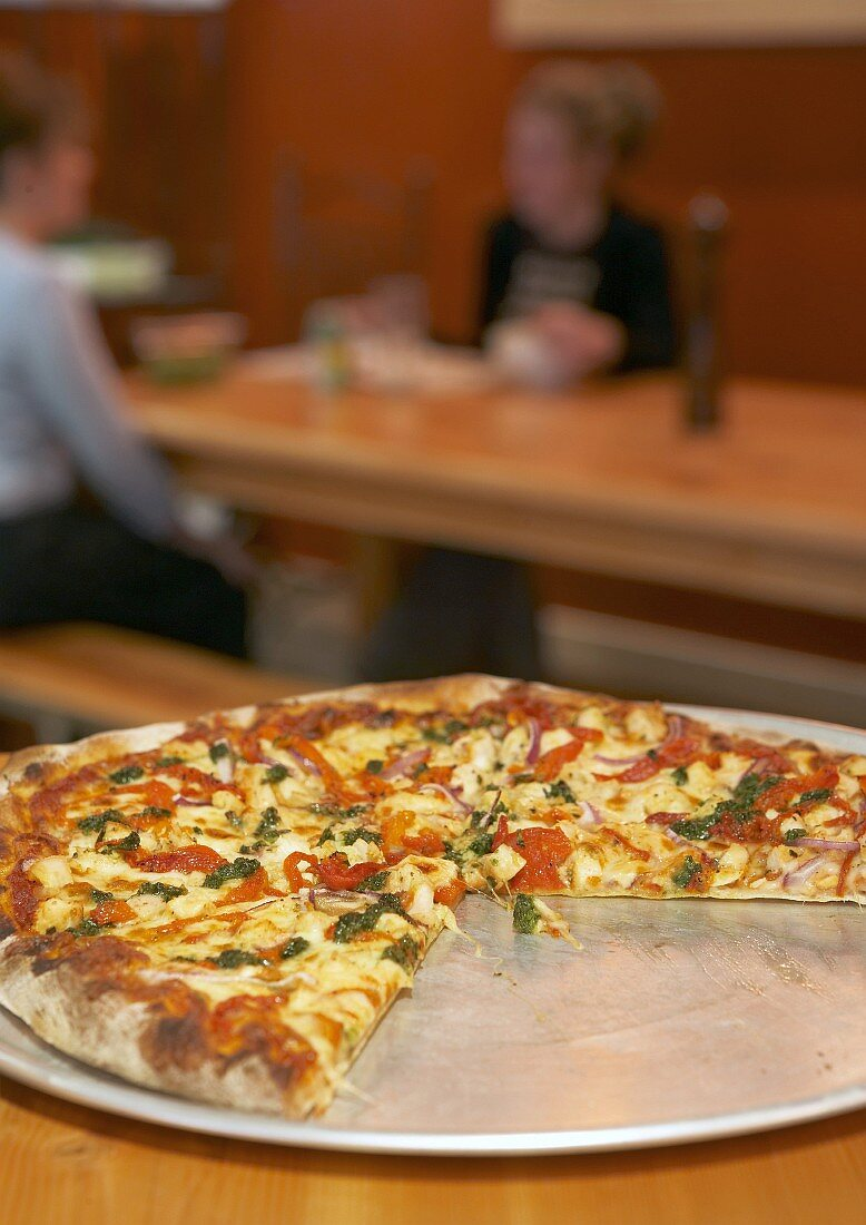 Pizza with slices removed on pizza plate in restaurant