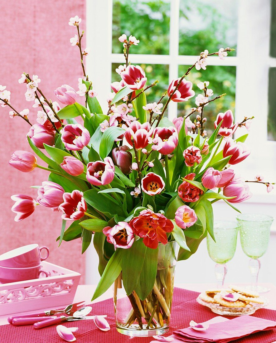 Tulips and ornamental cherry blossom in glass vase