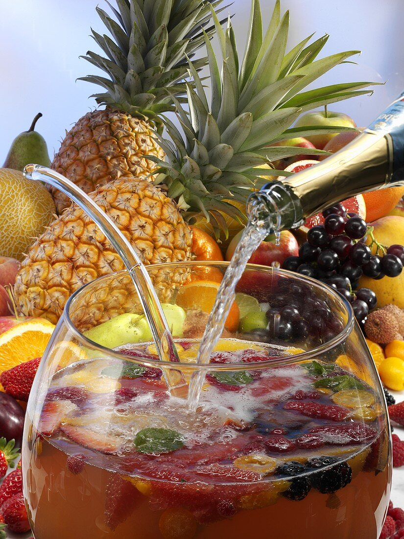 Pouring sparkling wine into fruit punch