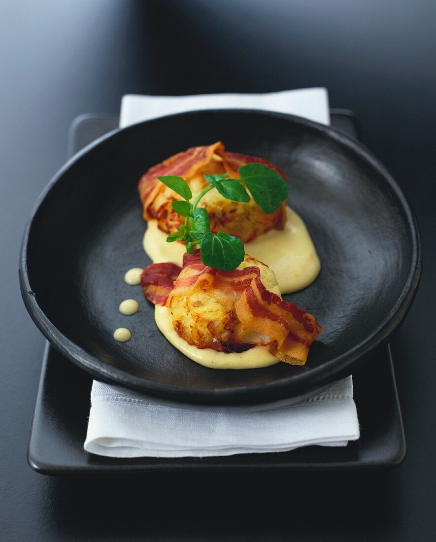 Oven-baked smoked fish cakes with bacon and curry sauce