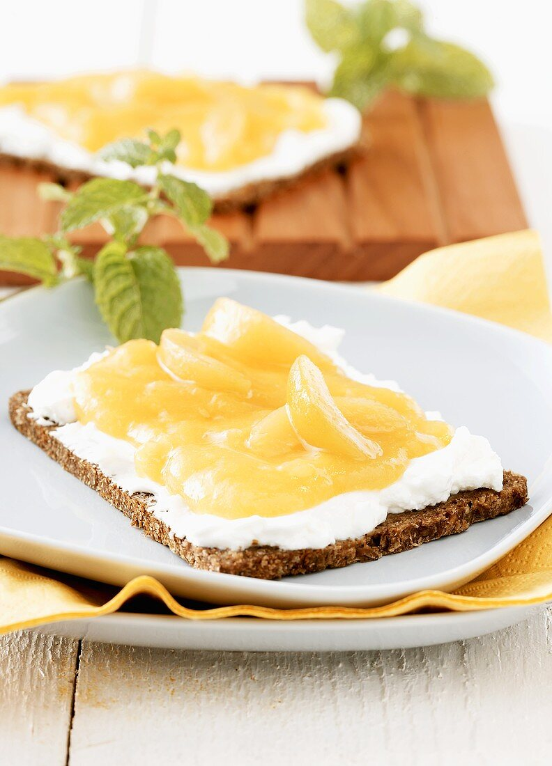 Whole-grain rye bread with soft cheese and apricot spread