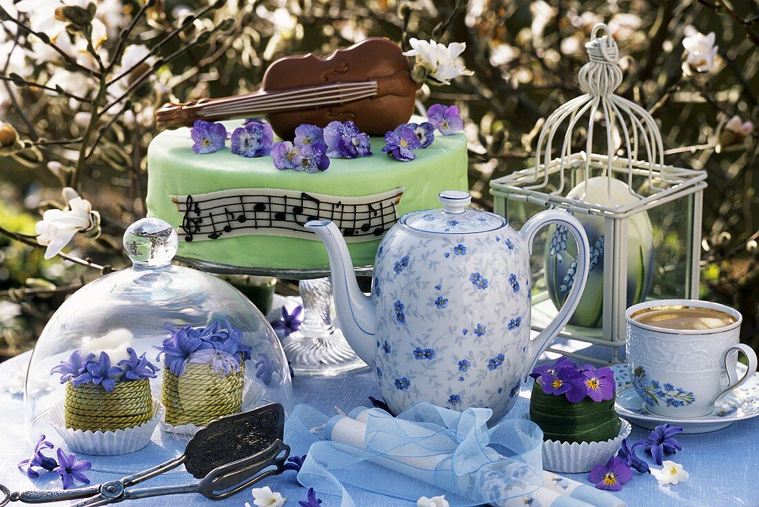 Table with coffee and marzipan cake out of doors (spring)