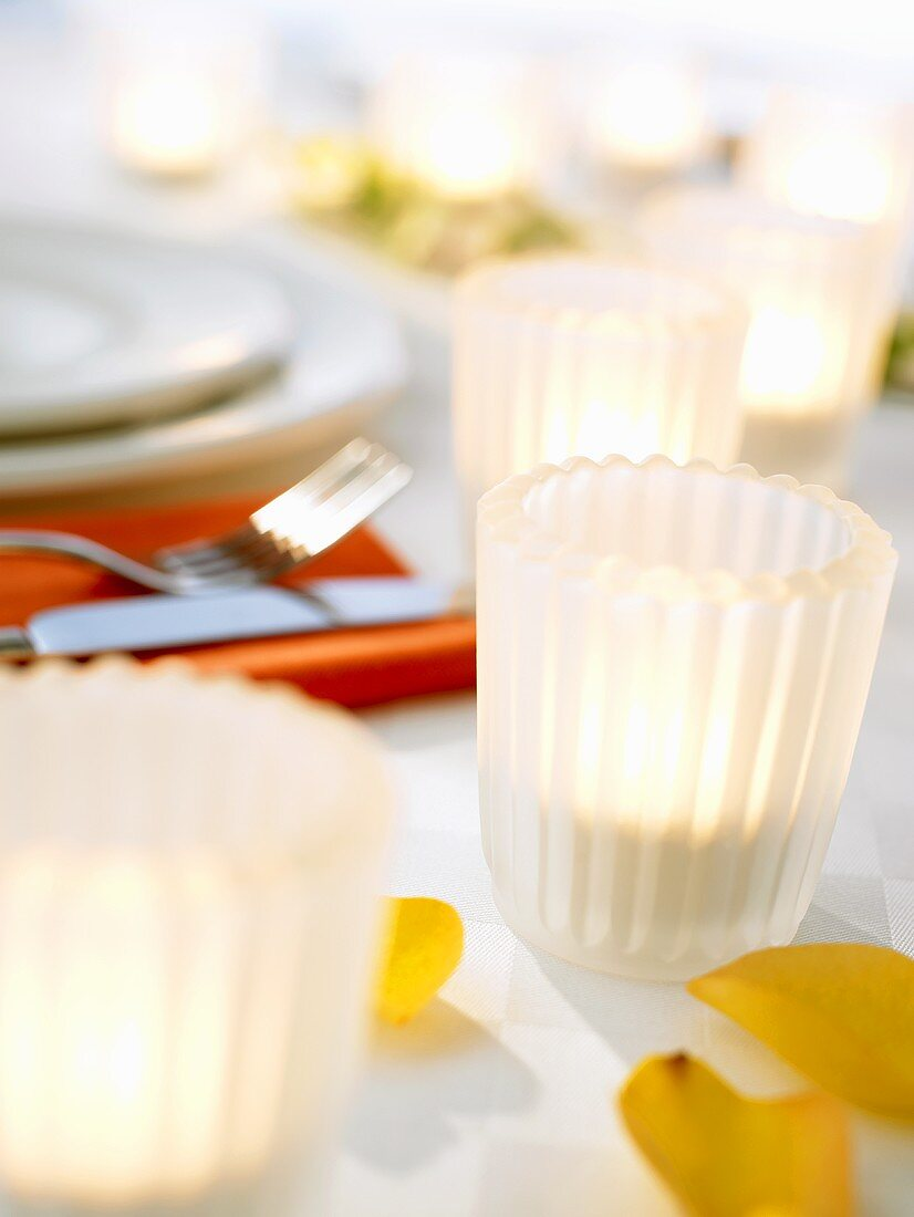 Tea lights in white glasses on laid table