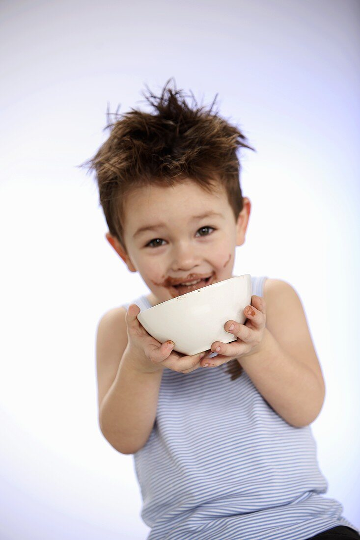 Small boy licking out bowl