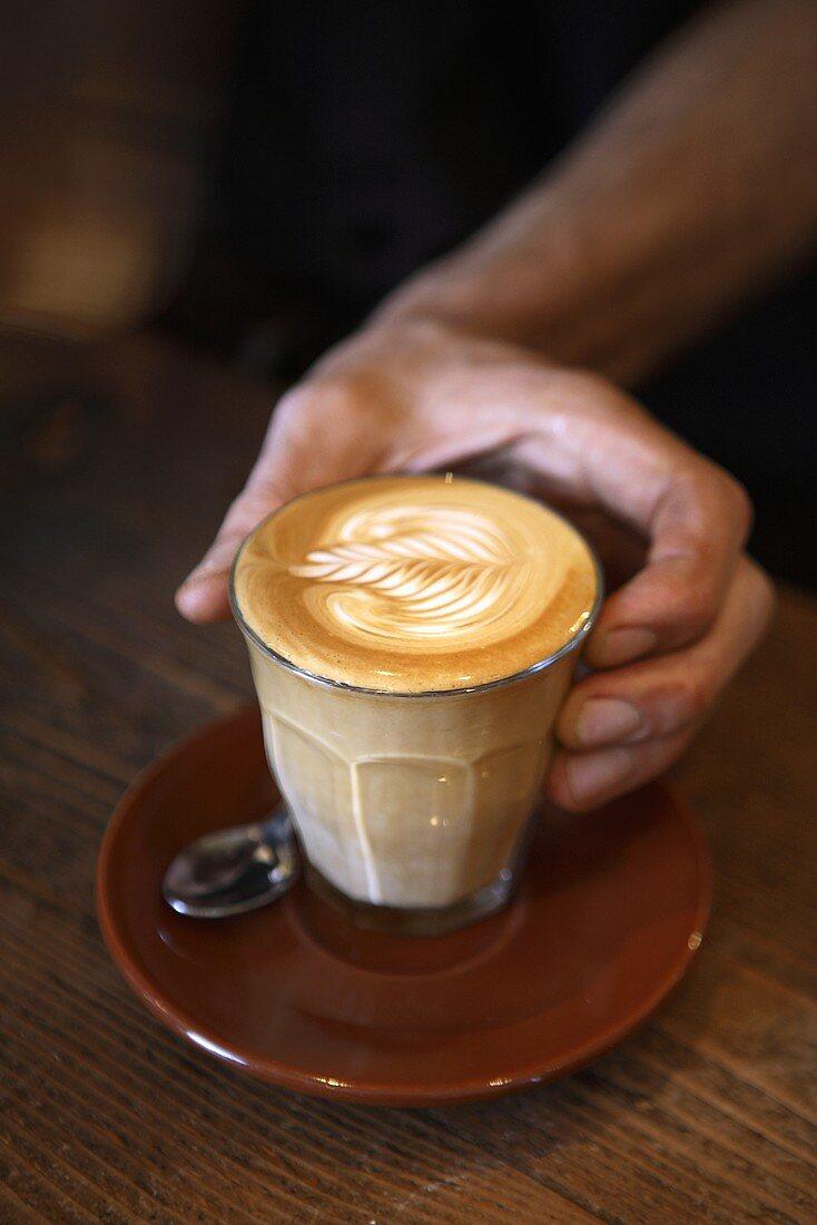 Barista holding a glass of caffè latte