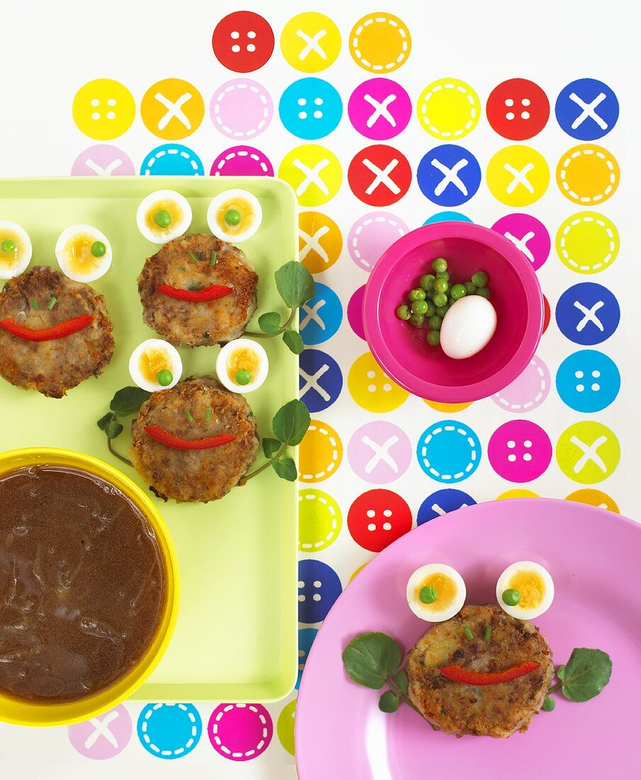 Amusing faces made with meat patties, boiled eggs and peas
