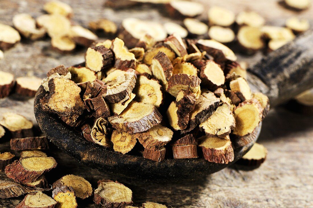 Dried Ural liquorice root on wooden spoon