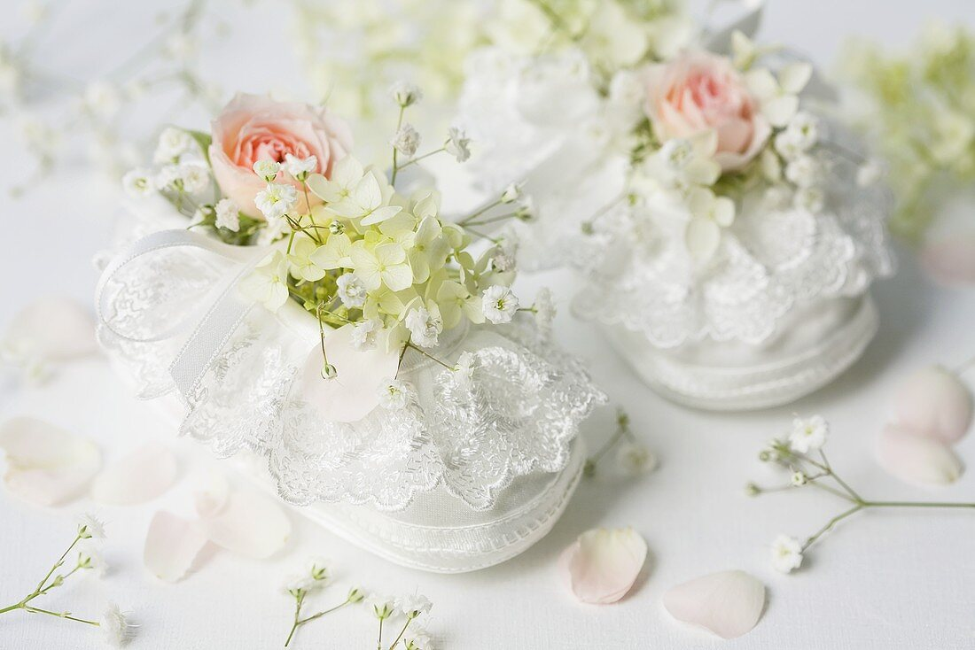 White baby shoes with roses and gypsophila