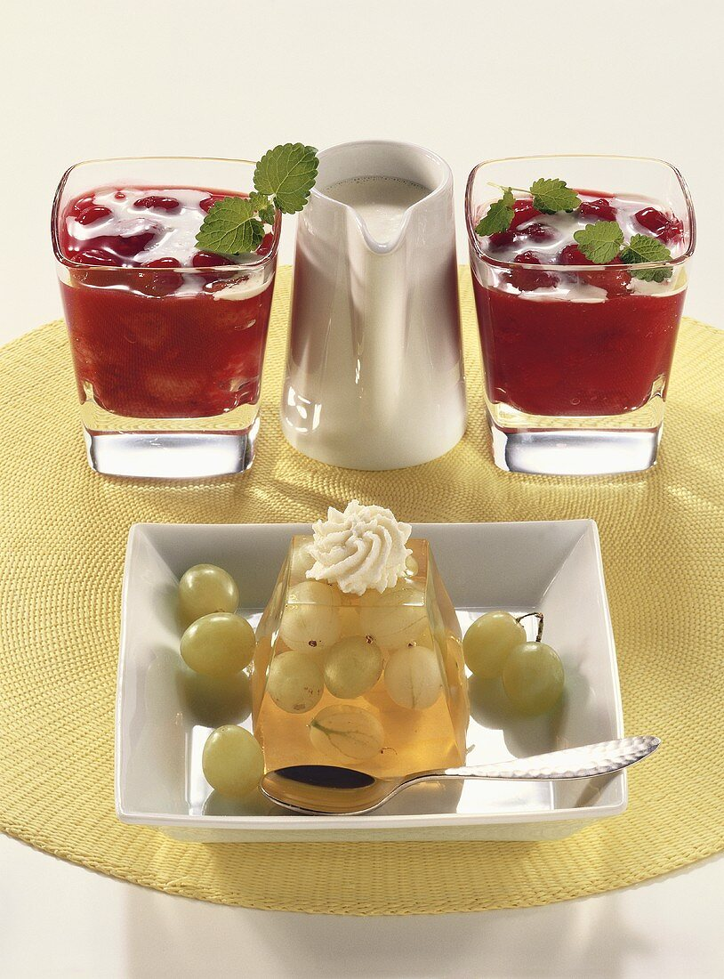 Grape and gooseberry jelly and red berry compote with cream