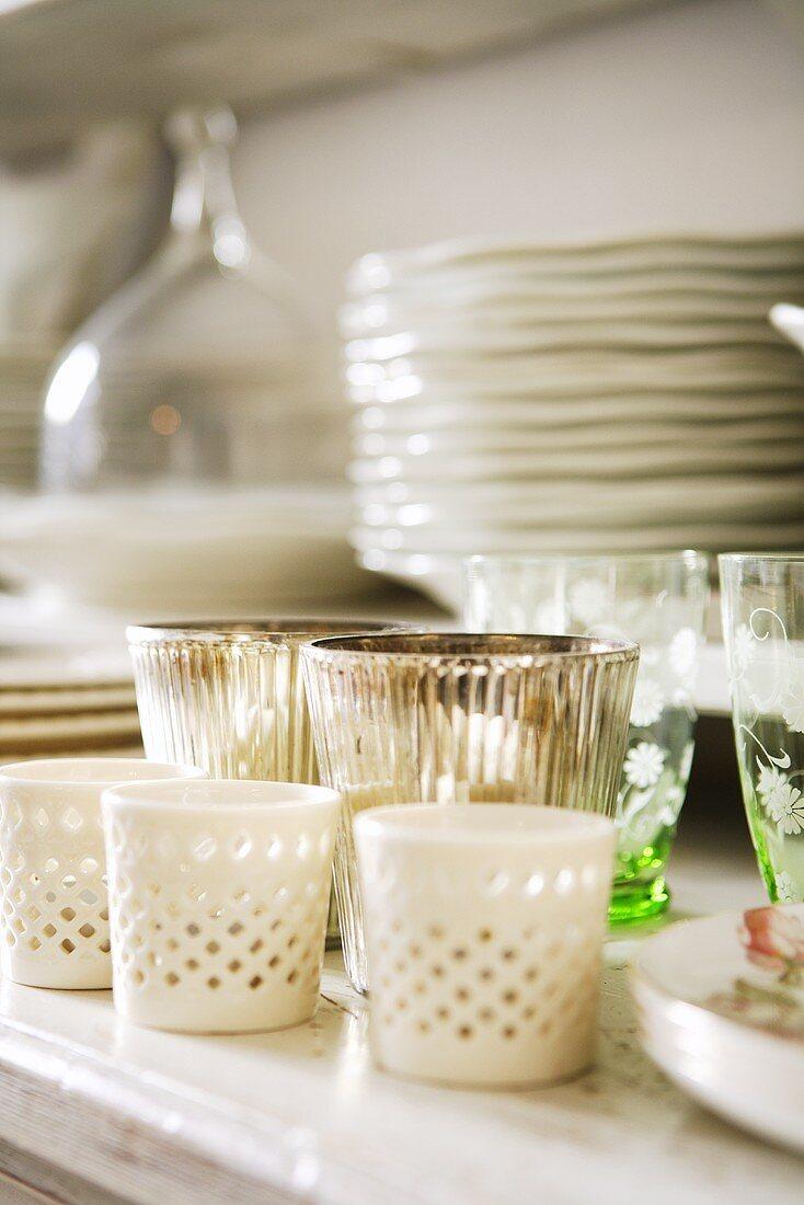 Crockery, glasses and tealights in holders in cupboard