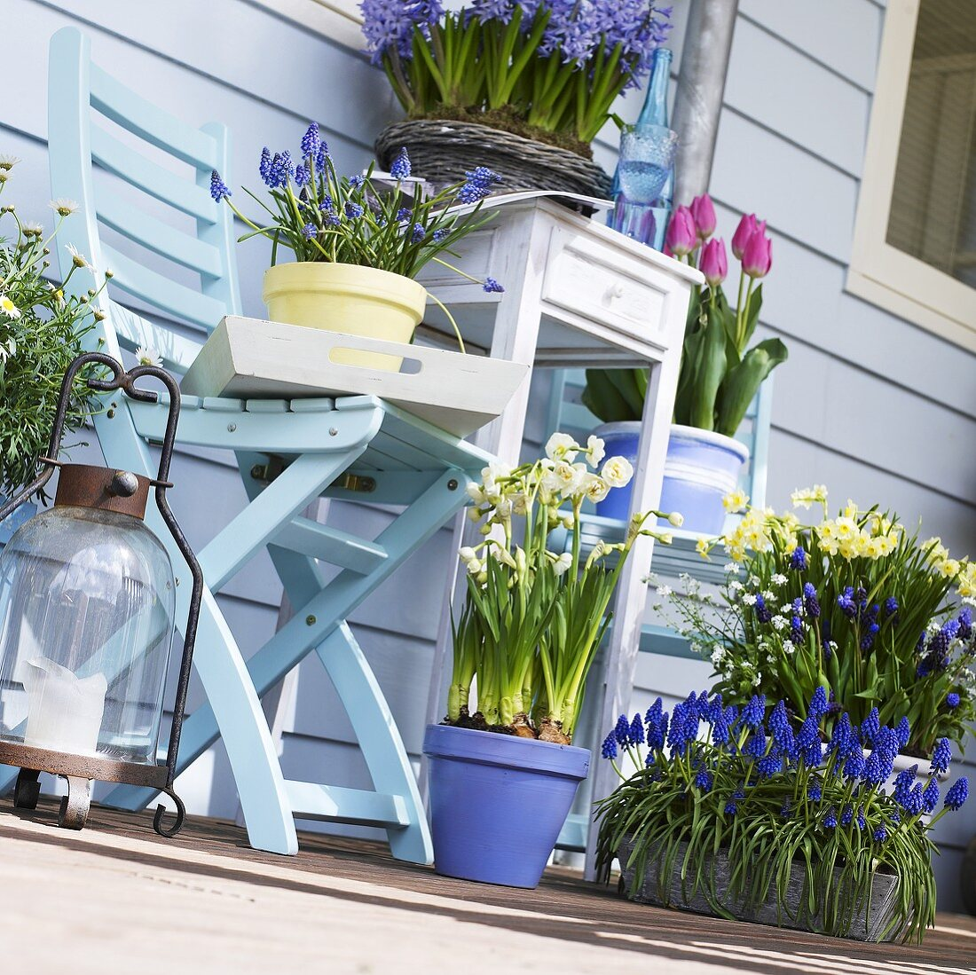 Various types of spring flowers in pots on a balcony