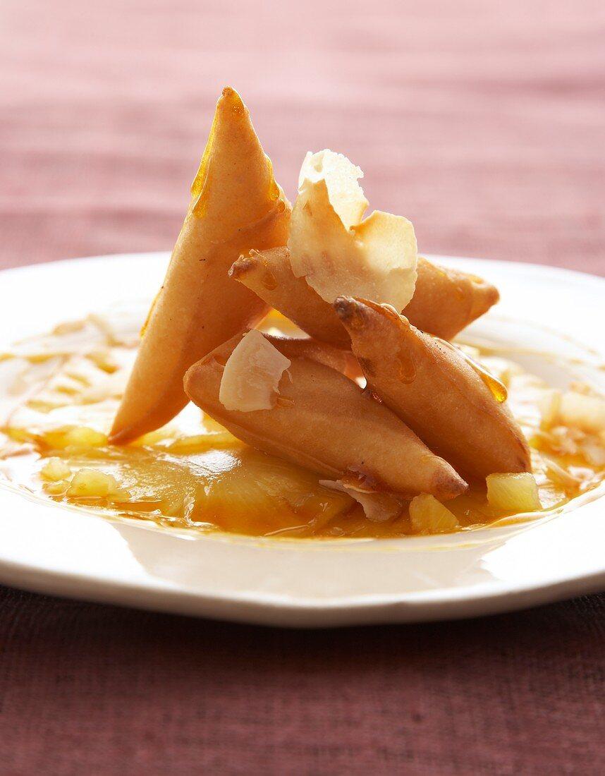 Coconut samosas on pineapple carpaccio and saffron syrup