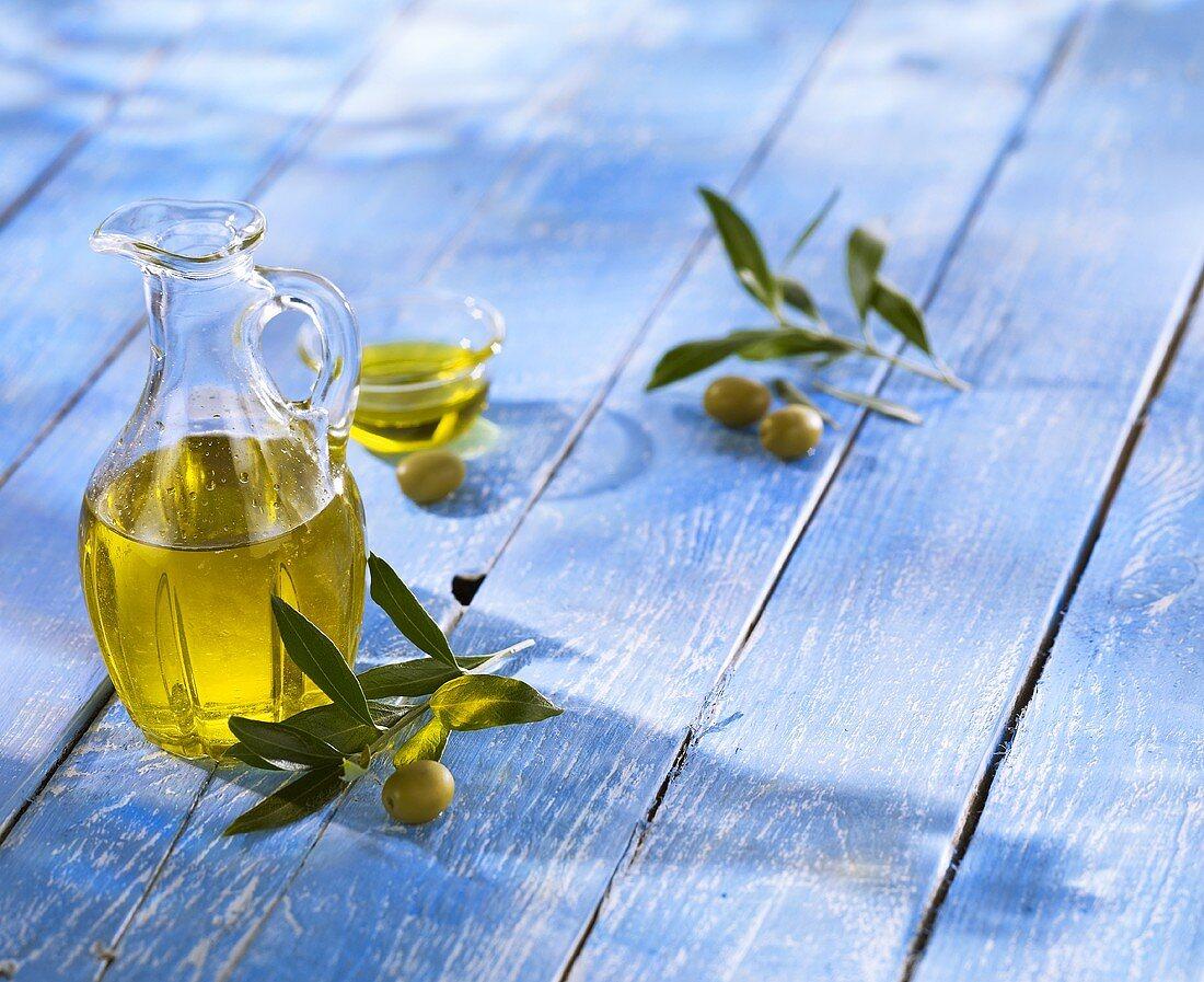 Olive oil, green olives and olive sprigs