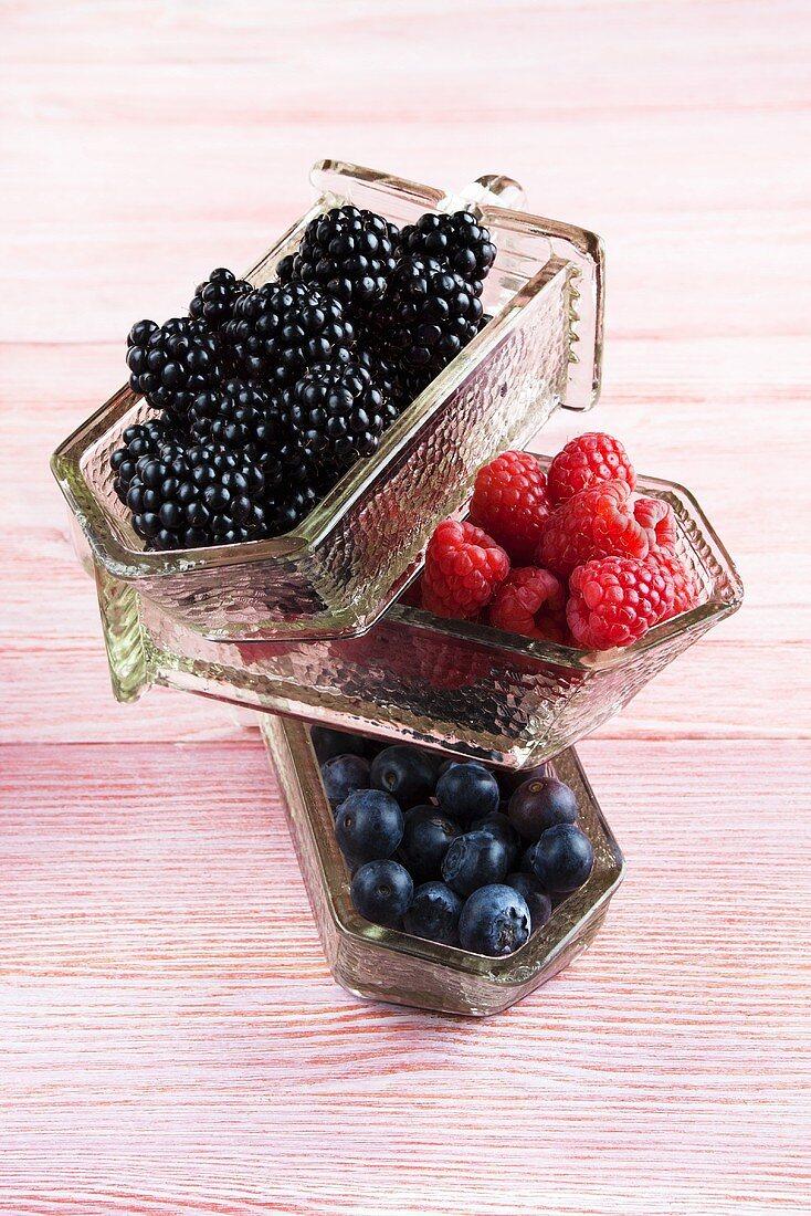Blackberries, raspberries and blueberries in glass receptacles