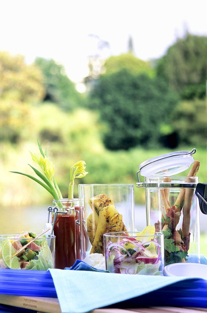 Assorted salads and appetisers on table by pond