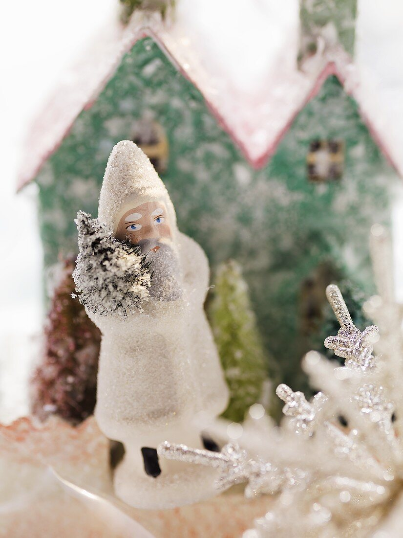 Father Christmas in front of cardboard house (Christmas decoration)