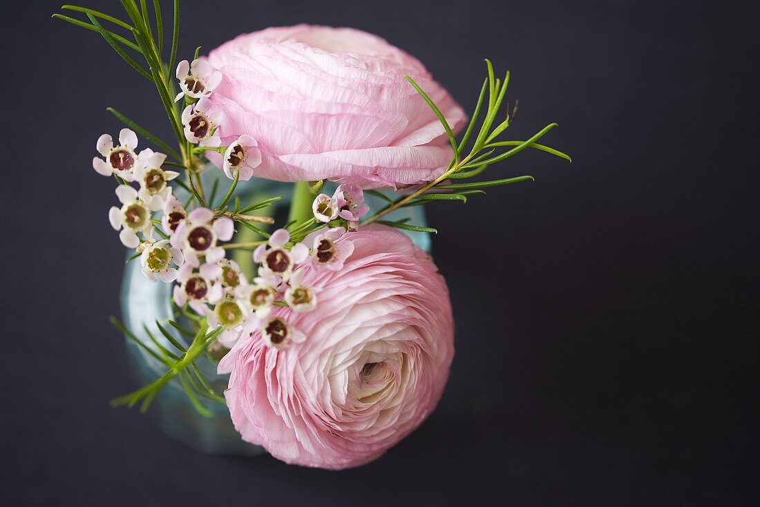 A spring bouquet with pink buttercups in a vase
