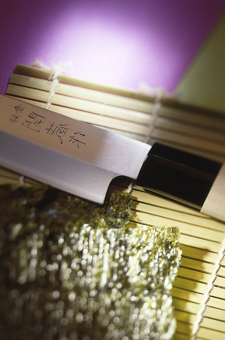 Nori leaves and a knife on a bamboo mat (Japan)