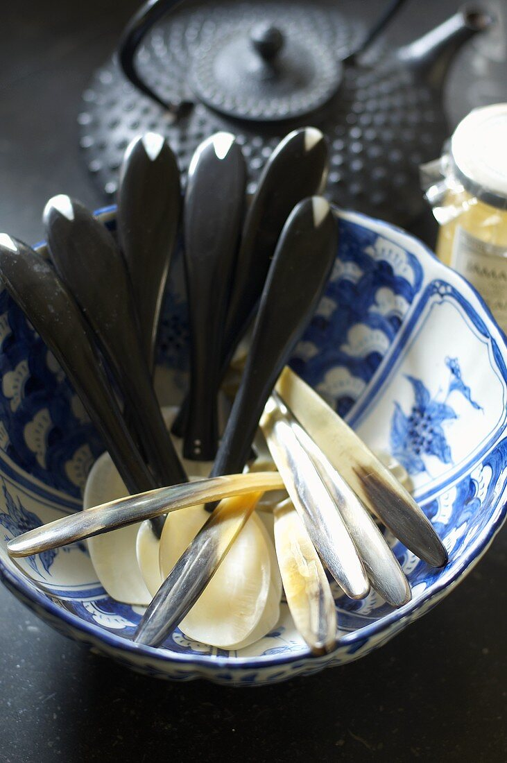 Horn spoons in an oriental porcelain bowl with a teapot in the background