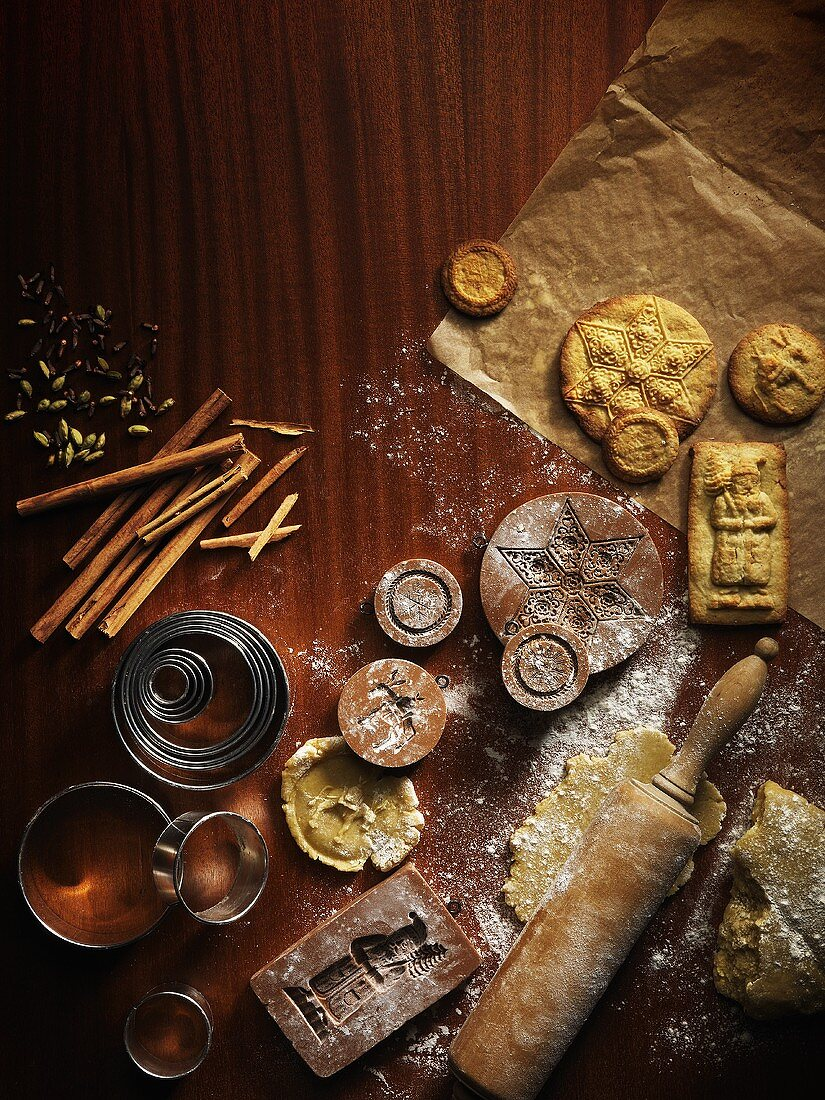 An arrangement of wooden moulds, cutters, Spekulatius (German Christmas shortcrust biscuits) and dough