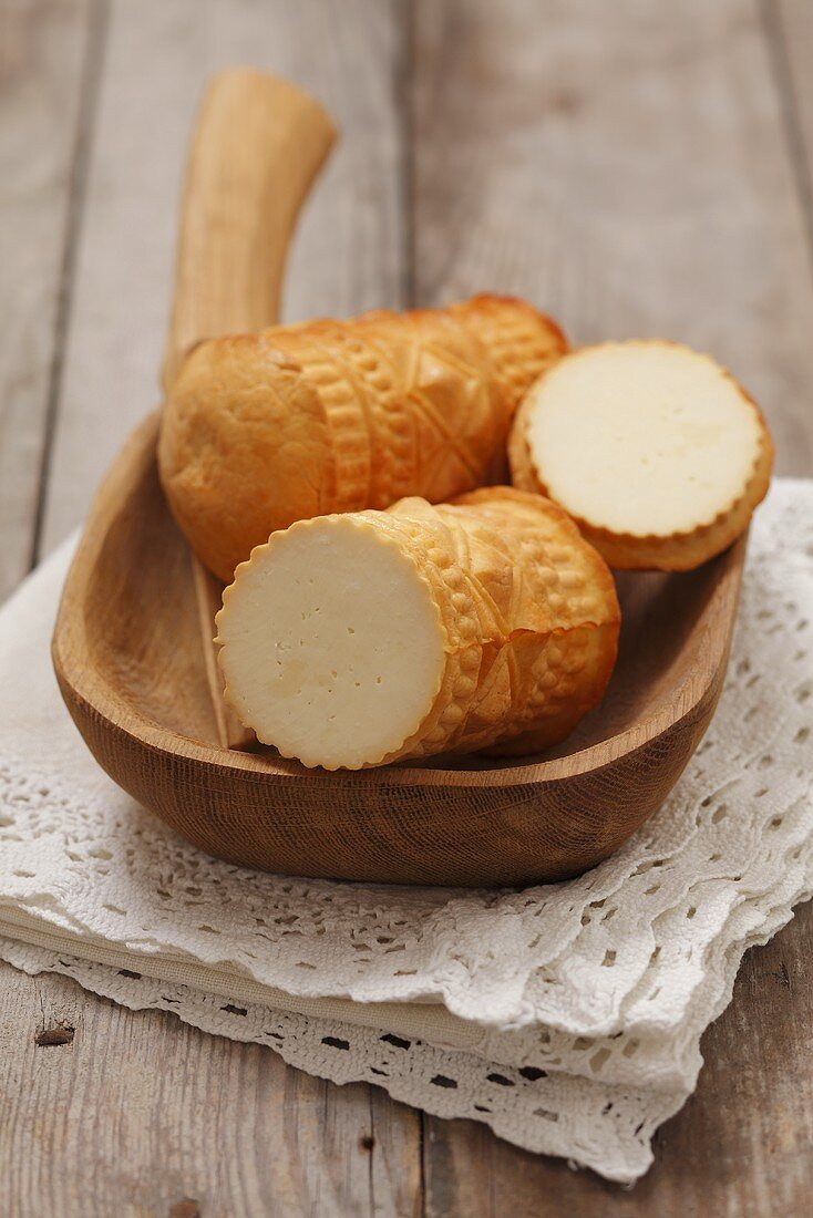 Oscypek (hard cheese made of sheep's milk, Poland), in a wooden bowl