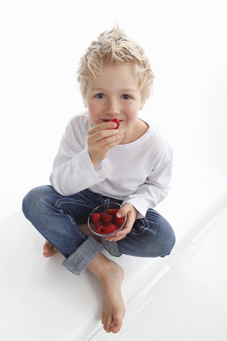 A little boy eating fresh raspberries