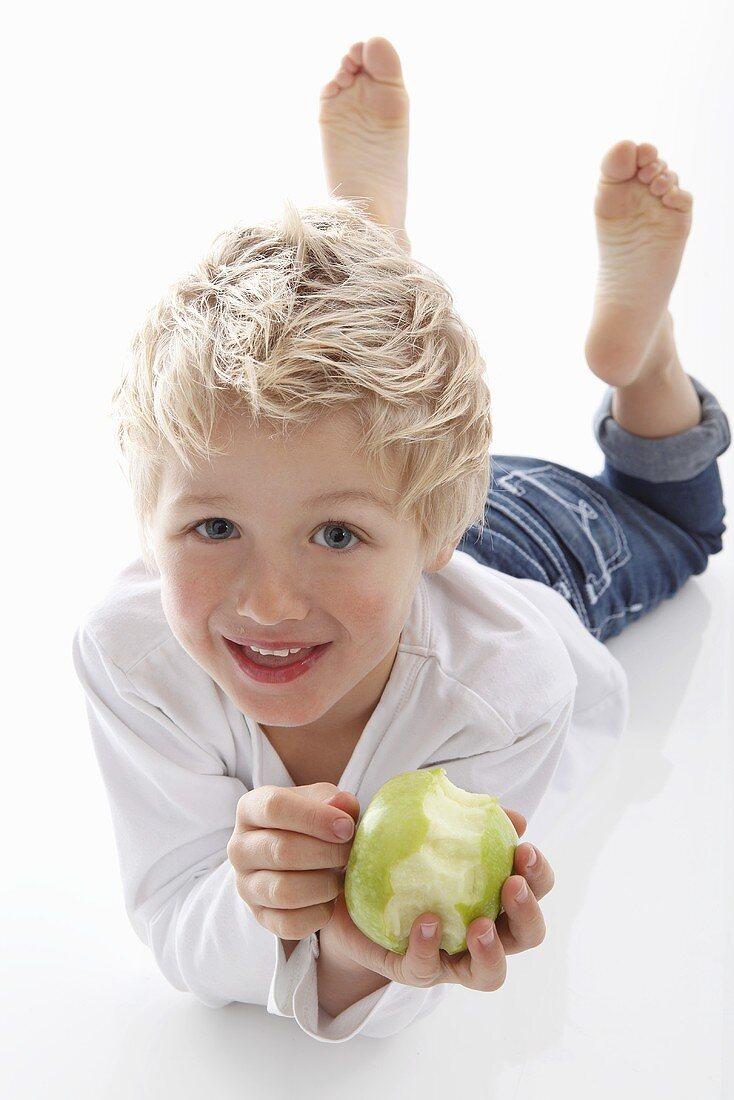 Little boy holding a partly eaten apple