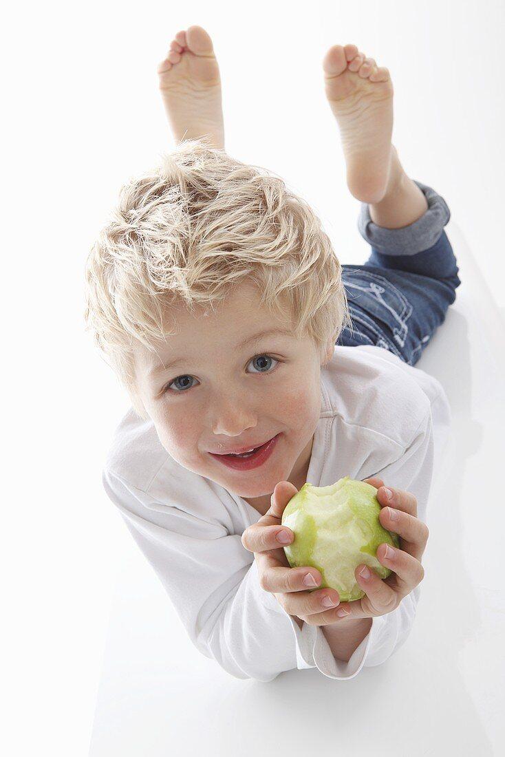 A little boy holding a half eaten apple