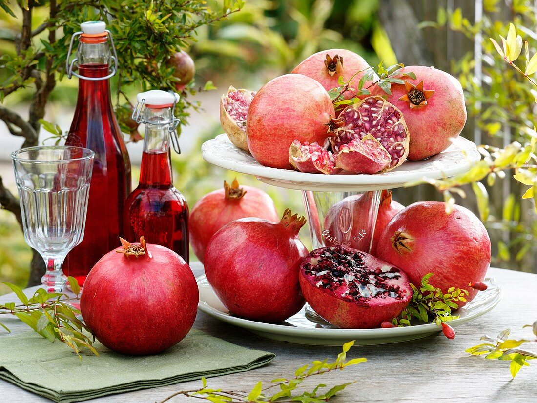 Pomegranates on tiered stand and bottles of pomegranate juice