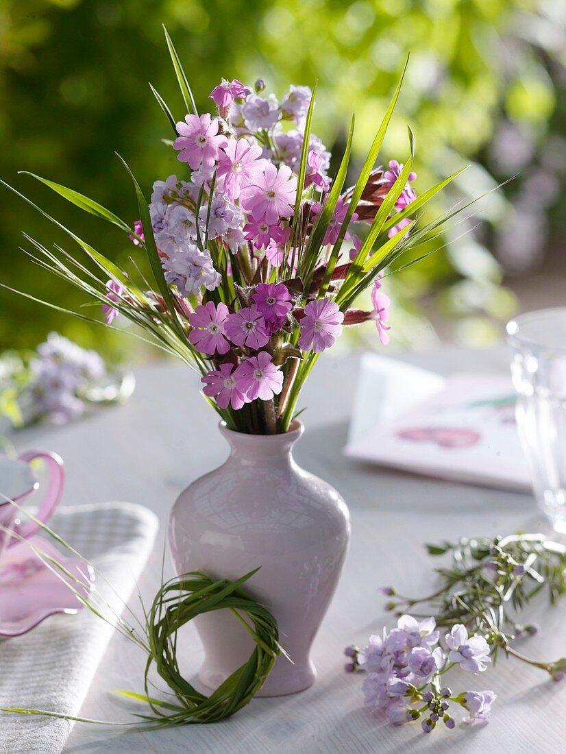 Frühlingsblumenstrauss und Kränzchen aus Gras als Tischdeko